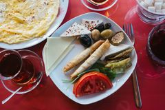 Piatto con alimento vegetariano - panino con gli ortaggi freschi formaggio ed olive accanto a vetro con la bevanda sul caffè ross Immagine Stock
