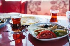 Piatto con alimento vegetariano - panino con gli ortaggi freschi formaggio ed olive accanto a vetro con le bevande sul caffè ross Immagini Stock