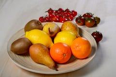 Piatto con frutta ed i pomodori Fotografie Stock