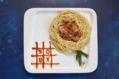 Piatto con gli spaghetti e la cotoletta, pittura della salsa del tic-TAC-dito del piede Scherza il menu Fotografia Stock Libera da Diritti
