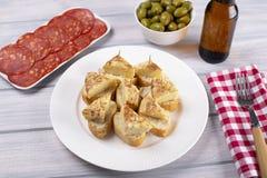 Piatto con i cappucci dell'omelette con pane accanto al piatto con chorizo, la ciotola con le olive e una birra fredda sulla tavo fotografia stock