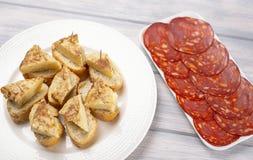 Piatto con i cappucci dell'omelette con pane accanto al piatto con chorizo sulla tavola di legno fotografie stock libere da diritti