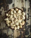 Piatto con i pistacchi salati in una ciotola di legno su fondo rustico di legno, vista superiore fotografia stock libera da diritti