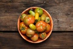 Piatto con i pomodori su vecchio fondo di legno Fotografia Stock