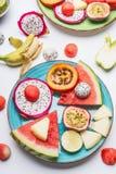 Piatto con i vari frutti tropicali affettati variopinti di estate e bacche su fondo bianco, vista superiore fotografia stock libera da diritti