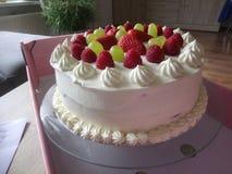 Piatto con il bello dolce crema montato con le fragole e l'uva sulla cima fotografia stock libera da diritti