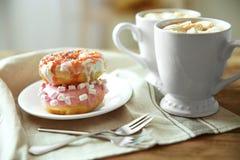 Piatto con le ciambelle e le tazze di caffè deliziose Immagine Stock