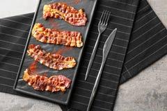 Piatto con le fette di lardo fritte del bacon sulla tavola fotografia stock