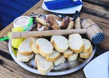 Piatto con le gambe e gli artigli bolliti del granchio marrone con pane ed immersione sulla tavola di legno immagini stock