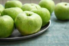 Piatto con le mele verdi fresche sulla tavola di legno Fotografia Stock Libera da Diritti