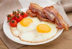 Piatto con le uova fritte, bacon a bordo immagine stock libera da diritti