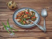 Piatto con le verdure ed i pezzi appeni preparato di pollo su un fondo di legno Piume della cipolla verde e sale grosso, sale immagine stock libera da diritti
