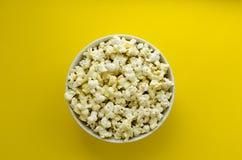 Piatto con popcorn su fondo di carta giallo fotografia stock