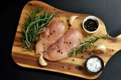 Piatto crudo fresco crudo del raccordo del petto di pollo con i rosmarini, il pepe, il sale e l'aglio sul bordo di legno e sul fo immagini stock