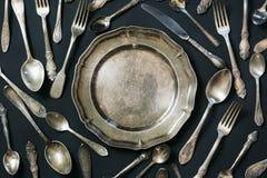 Piatto, cucchiai, forcelle, coltelli, modello dell'argenteria su fondo nero Struttura della cucina Fotografia Stock Libera da Diritti