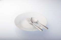 Piatto, cucchiaio e forchetta bianchi Fotografia Stock