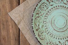 Piatto d'annata vuoto di sollievo sul tovagliolo di tela sulla tavola di legno della plancia, vista superiore, disposizione piana Immagini Stock Libere da Diritti