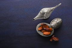 Piatto d'argento con le date e lampada di aladdin su fondo di legno blu scuro Priorit? bassa di Ramadan Ramadan Kareem fotografia stock