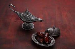 Piatto d'argento con le date e lampada di aladdin su fondo di legno rosso scuro Priorit? bassa di Ramadan Ramadan Kareem fotografia stock