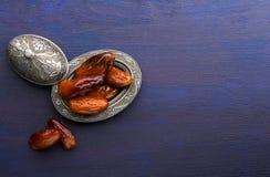 Piatto d'argento con le date su fondo di legno blu scuro fotografia stock libera da diritti
