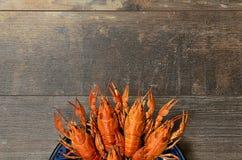 Piatto dei gamberi rossi sulla vecchia tavola di legno nella parte inferiore Fotografie Stock