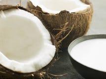Piatto del latte di noce di cocco con una noce di cocco fresca di spaccatura Immagine Stock