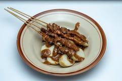 Piatto del lontong dei dolci di riso con i bastoni satay dall'Indonesia fotografia stock libera da diritti