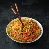 Piatto del mein, delle tagliatelle e delle verdure del cibo con i bastoncini di legno fotografia stock