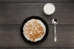 Piatto del porridge del riso e di un bicchiere di latte Immagini Stock