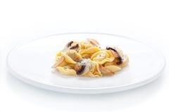 Piatto del Tortellini con i funghi e l'aglio sauteed fotografia stock