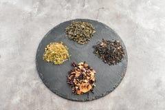 Piatto dell'ardesia con differenti tipi di tè asciutti su fondo grigio fotografia stock