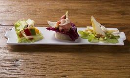 Piatto dell'entrata con il prosciutto di Parma, il fico, la pera, la lattuga porpora ed il g fresco Immagine Stock Libera da Diritti