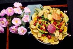 Piatto della foto con i frutti vicino ai fiori fotografie stock