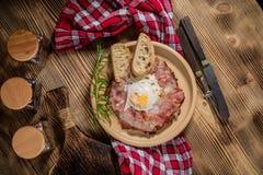 Piatto della prima colazione con le uova fritte, il bacon ed il pane Immagine Stock