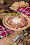 Piatto della prima colazione con le uova fritte, il bacon ed il pane Fotografia Stock