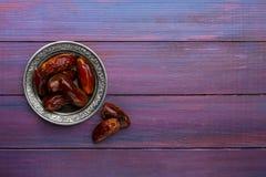 Piatto delle date su fondo di legno viola scuro Disposizione piana immagine stock