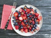 Piatto delle fragole, mirtilli, estate antiossidante organica del prodotto delle uva spina su un fondo di legno immagini stock