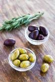 Piatto delle olive verdi e nere su superficie di legno Immagini Stock