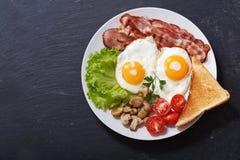 Piatto delle uova fritte, del bacon, dei funghi, dell'insalata e del pane tostato, vista superiore fotografia stock