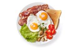 Piatto delle uova fritte, del bacon, dei funghi e del pane tostato sul backgro bianco immagine stock