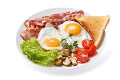 Piatto delle uova fritte, del bacon, dei funghi e del pane tostato sul backgro bianco fotografia stock libera da diritti