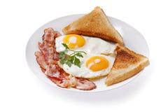 Piatto delle uova fritte, del bacon e del pane tostato su fondo bianco immagini stock