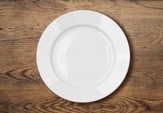 Piatto di cena vuoto bianco sulla superficie di legno della tavola Fotografie Stock
