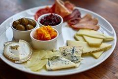 Piatto di formaggio con differenti generi di formaggio con le erbe e le noci del timo Fotografia Stock