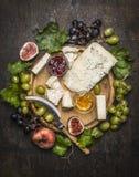 Piatto di formaggio con gorgonzola e formaggio del camembert con il coltello per l'uva del formaggio, il miele e l'inceppamento b fotografie stock