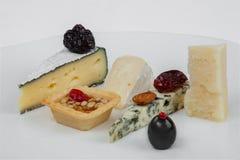 Piatto di formaggio con i dadi, i datteri, le mandorle e le olive immagini stock