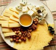 Piatto di formaggio con parecchi generi di formaggio, di dadi e di miele Fotografia Stock Libera da Diritti