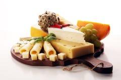 Piatto di formaggio servito con l'uva, vario formaggio su un vassoio fotografie stock