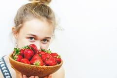 Piatto di legno con le fragole in mani della ragazza su fondo leggero immagine stock libera da diritti