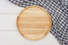 Piatto di legno del giro vuoto con la tovaglia grigia del percalle sulla tavola di legno bianca fotografia stock